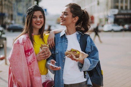 Happy girls walking around city with hot dogs