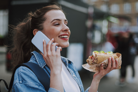 Happy female talking by phone with hot dog