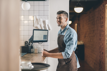 Smiling young waiter in front of the bar counter 版權商用圖片