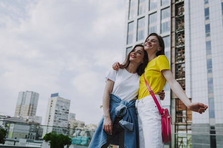 Two happy hipster girls embracing on city view