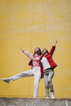 Two pretty cheerful hipster girls enjoying life