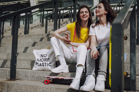 Two happy skater girls sitting on stairs Banco de Imagens