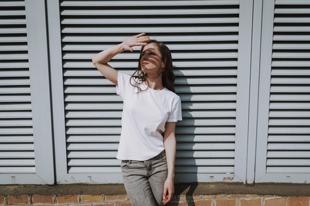 Happy hipster girl covering face by hand from sun