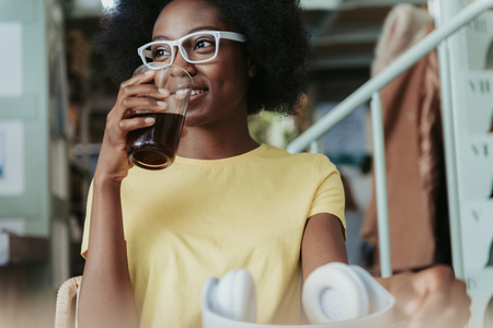 Low angle of beautiful African woman having rest in cafeteria