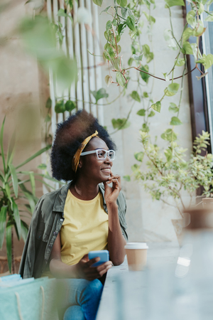 Waist up of African lady wearing casual and having rest in cafe Stock Photo