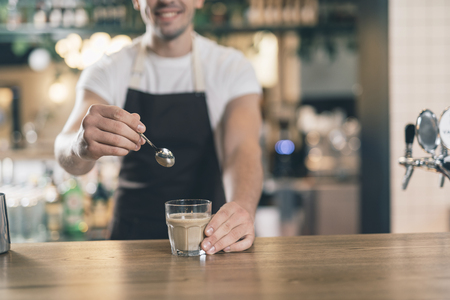 Smiling barista holding spoon near the glass of cocoa