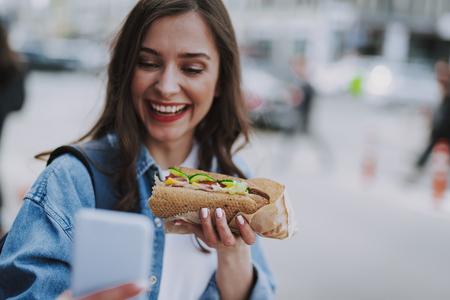 Joyful female making selfie with hot dog
