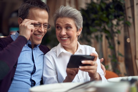 Cheerful aged couple looking at mobile phone
