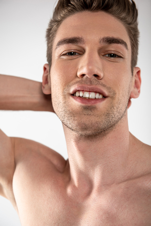 Attractive young man with stubble expressing positive emotions
