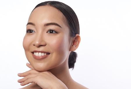Femme heureuse isolée touchant son menton et souriant Banque d'images