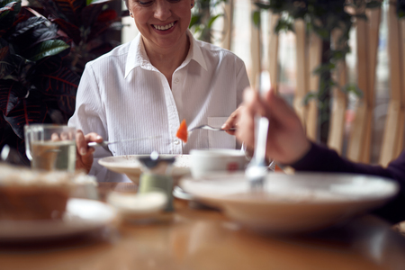 Smiling woman eating salad in cafe with man
