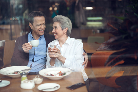 Smiling elegant aged couple happy to meet in cafe