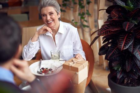 Happy smiling elegant aged female in cafe Imagens