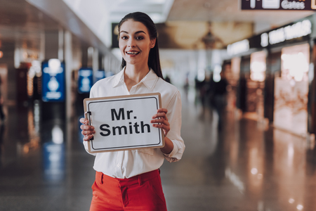 Easy-going girl is meeting guest arriving at airport