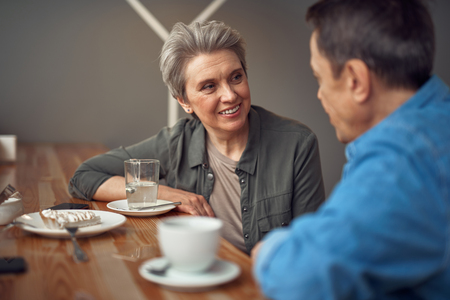 Happy smiling aged couple sitting in cafe
