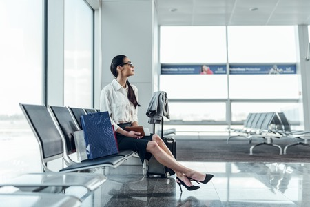 Calm woman is expecting her flight in lobby Stockfoto - 123119472