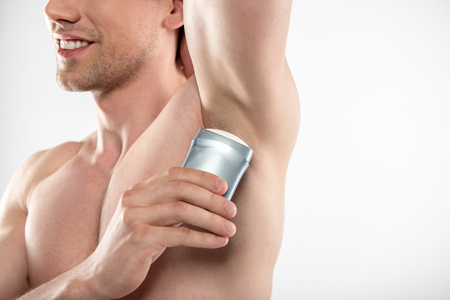 Joyful young man applying antiperspirant on armpit