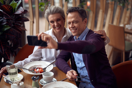 Happy aged lady and man making selfie in cafe