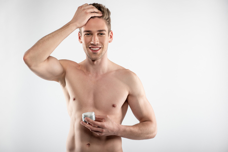 Joyful young man with perfect muscular body holding jar of cosmetic cream