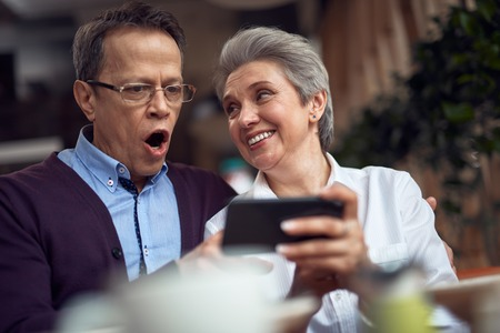 Shocked mature man look at smth in mobile phone