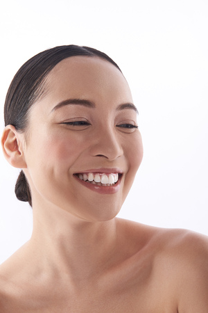 Positive portrait of smiling Asian lady on the white background