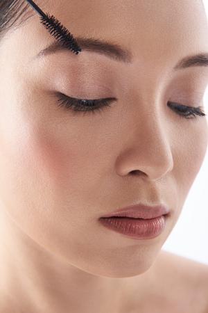 Portret van kalme vrouw met mascaraborstel dichtbij haar wenkbrauw Stockfoto