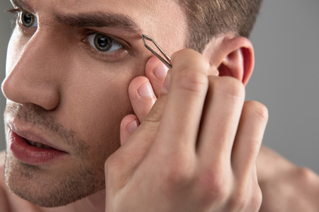 Handsome young man plucking eyebrows with tweezers