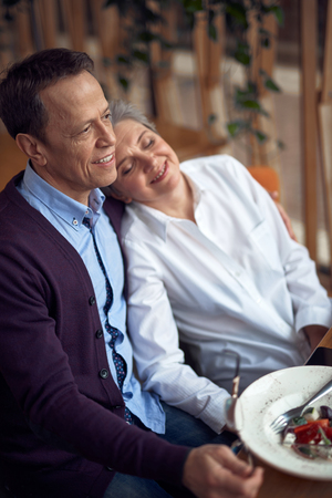 Happy beloved aged couple sitting in cafe