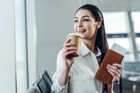 Delighted young woman is expecting flight with hot drink