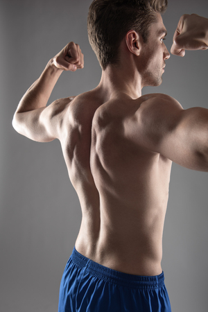 Handsome young man demonstrating his muscular body