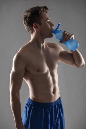 Handsome young man with perfect body drinking water Stok Fotoğraf