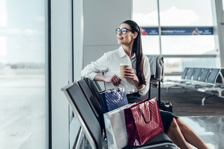 Happy young woman is enjoying hot drink in airport