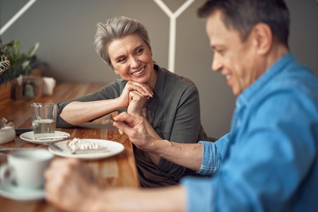 Cheerful aged couple enjoying meeting in cafe