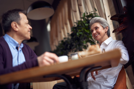 Aged male and female couple meeting in cafe