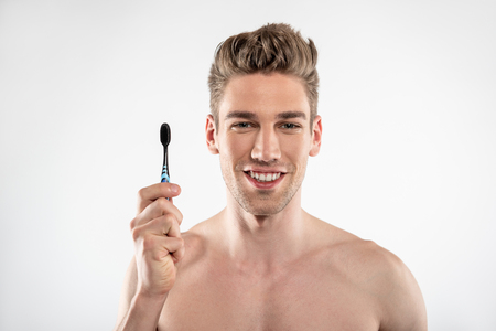 Joyful young man with stubble holding toothbrush