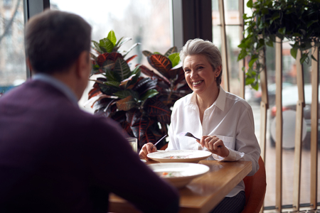 Gray haired elegant lady meeting with man in cafe