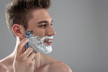 Lächelnder junger Mann, der sich mit Einwegrasierer rasiert