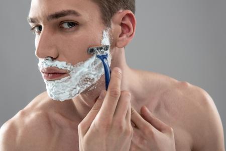 Hübscher junger Mann, der sich mit Einwegrasierer rasiert