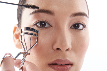Close up of woman getting eyelashes curled and looking serious