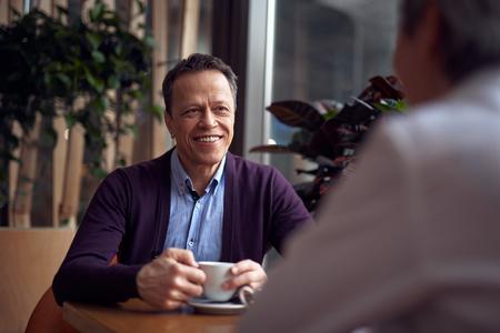 Middle aged elegant smiling man sitting in cafe Stok Fotoğraf