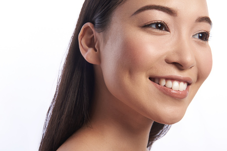 Pretty Asian woman looking happy and smiling with teeth revealed 스톡 콘텐츠