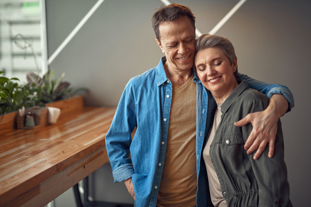 Happy smiling aged couple embracing in cafe