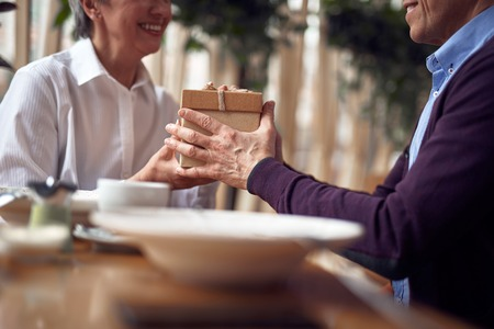 Aged man giving present box to happy lady