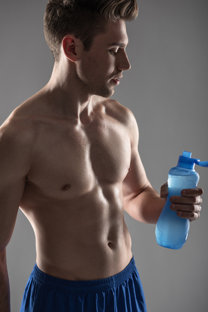 Handsome young man with perfect body drinking water after workout Stok Fotoğraf