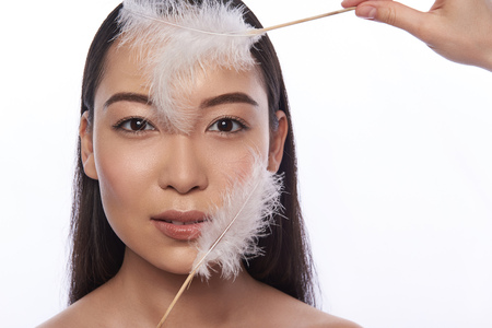 Asian woman with two soft feathers touching her face 스톡 콘텐츠
