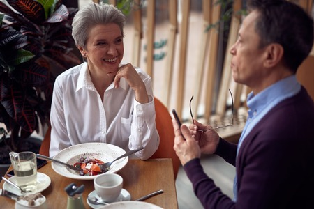 Happy aged lady and man having discussion