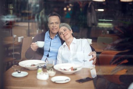 Happy elegant aged couple enjoying dinner in cafe