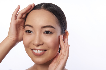 Cheerful young lady touching her face and looking happy