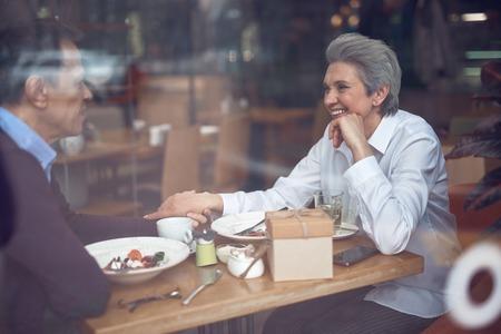 Happy elegant aged couple enjoying meeting in cafe