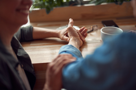Close up happy couple holding hands in cafe